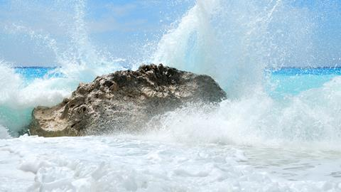 Waves splashing on a rock producing spray