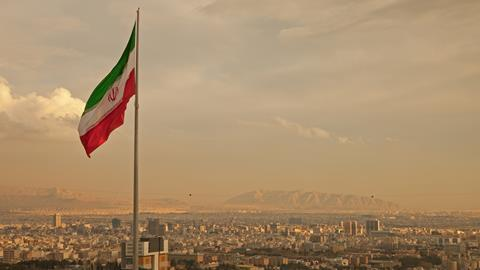 The Iranian flag flying above the Tehran skyline.