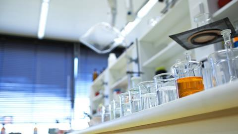 chemistry lab (shallow DOF; focus on the beakers in the foreground)