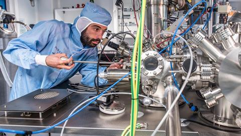 Corentin Durand makes adjustments to the ultrahigh vacuum chamber that houses the nanocar racetrack