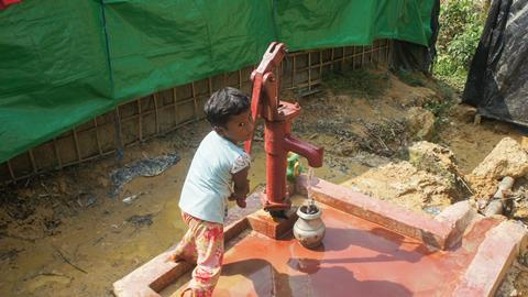 An image showing a small girl collecting water from tube well in Bangladesh