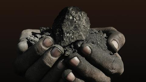 hands holding coal