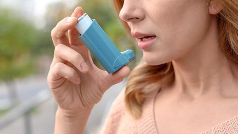 An image showing a woman using an inhaler