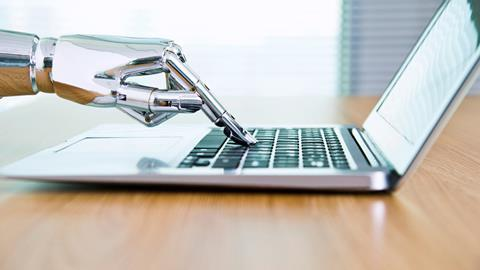 An image showing a robot's hand typing on a laptop