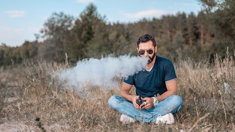 An image showing a man who is vaping