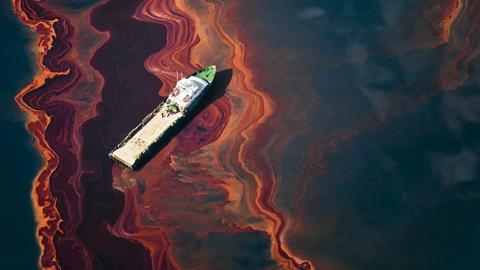 A ship drifts through a heavy band of oil, spilled from Deepwater Horizon wellhead in the Gulf of Mexico, May 2010.