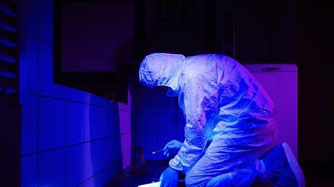 Technician collecting DNA evidence on place of crime under UV black light