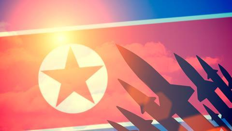 Rocket silhouettes against a background of the flag of North Korea