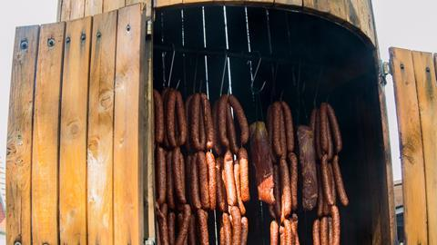 A photograph of meat in a smokehouse