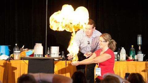 Steve Spangler igniting methane filled bubbles in the hands of a young teacher at Science in the Rockies 2011.