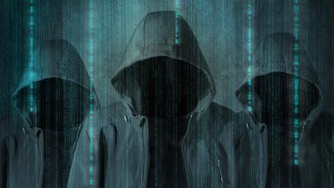Hooded figures with computer imagery in the background