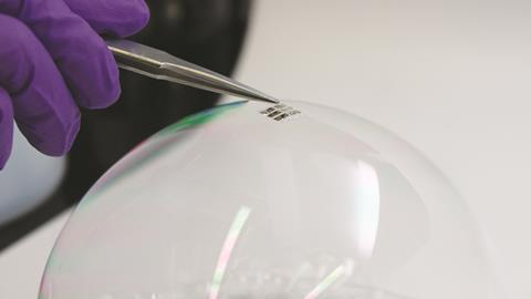 An ultra-lightweight solar cell is placed on the surface of an ordinary soap bubble