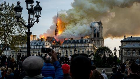 An image showing people watch the landmark Notre-Dame Cathedral burning in central Paris on April 15, 2019