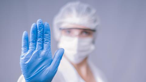 Researcher wearing lab PPE including gloves, eye protection and mask