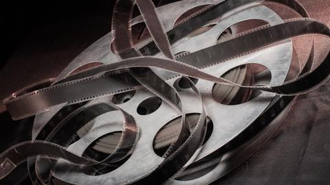 Movie reel lays on a black table