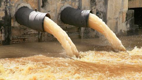 An image showing waste water pipes with water flowing into a river