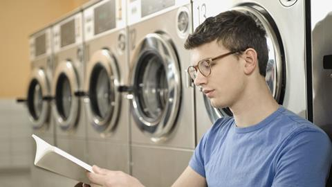 A photograph of a young man reading book in laundry