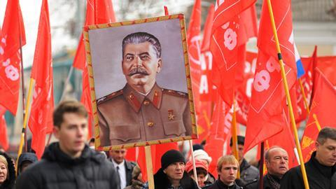 A man carries a portrait of Joseph Stalin at a Communist party meeting in Orel, Russia, November 7, 2015