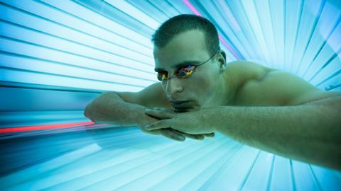 A man using a ultraviolet tanning bed
