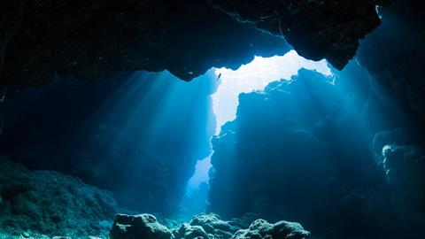 A photograph showing a ray of sunlight in an underwater cave