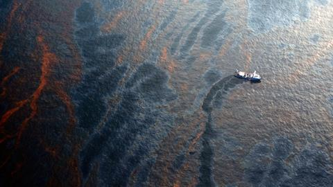 An image showing a coast guard attempting burning off oil leaking from sunken rig