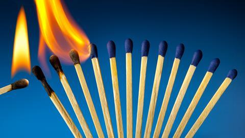 An image showing a row of closely positioned matches burning one by one in a domino effect fashion