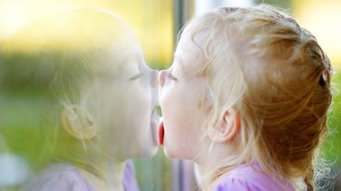 Girl licking her reflection on a window glass
