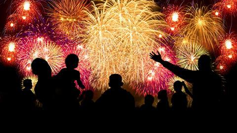 A photograph of a crowd of people watching a fireworks display