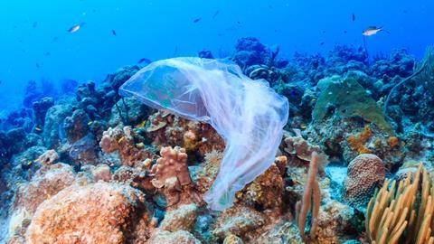 Plastic pollution: a discarded plastic rubbish bags floats on a tropical coral reef presenting a hazard to marine life