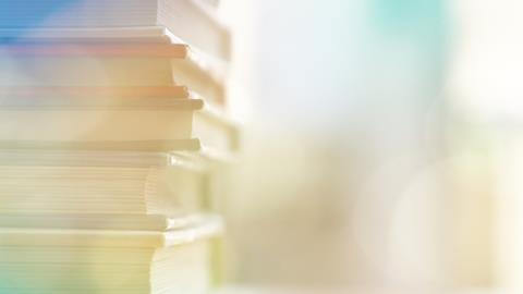 Shallow depth of field image showing close up of books piled high on desk and artificial lens flair obscuring dreamy style background