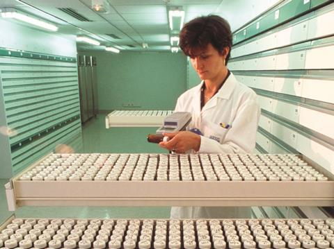 Female scientist using bar-code reader in a drug molecule library
