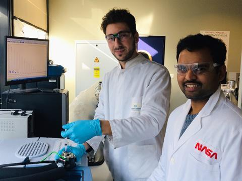 Photo of Lucas Lethuillier-Karl and Kalaivanan Nagarajan injecting a solution into a microfluidic infra-red spectroscopy cell