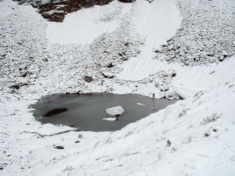 An image showing Roopkund Lake, with two people at the margins of the lake, giving a sense of scale