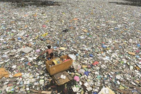 Collecting plastics from polluted river in Manila, Philippines