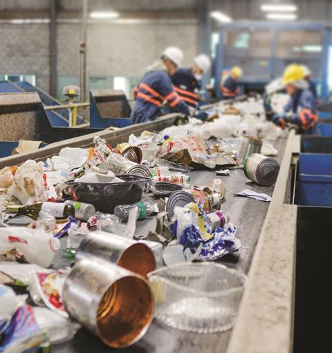 Mixed recycling on conveyor belt to be sorted by workers
