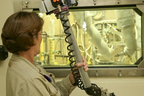 0418CW - Oak Ridge Feature - ORNL worker using mechanical arm to work inside hot cell