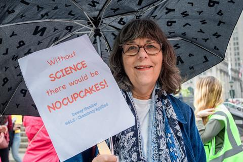 An image showing a woman holding a placard that reads