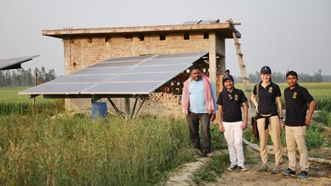 Image of the Oorja team in the countryside with a solar pump behind them