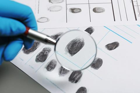 Criminologist examining fingerprints on paper