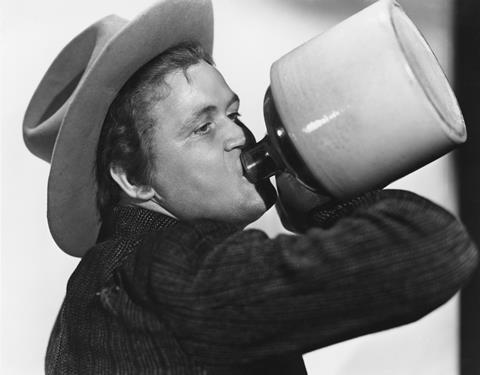 Man in cowboy hat drinking from a jug