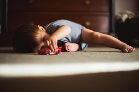 infant playing with toy cars