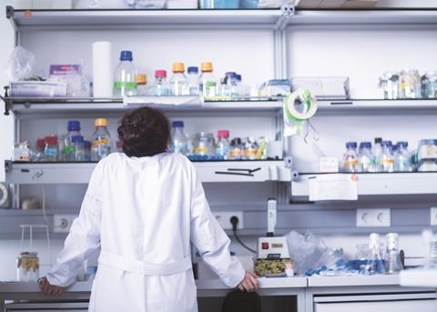Female scientist in laboratory looking at shelves
