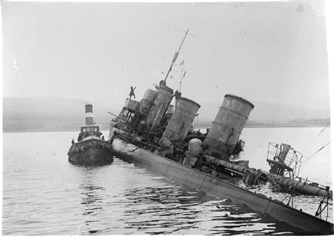 Tug alongside scuttled German destroyer G 102 at Scapa Flow
