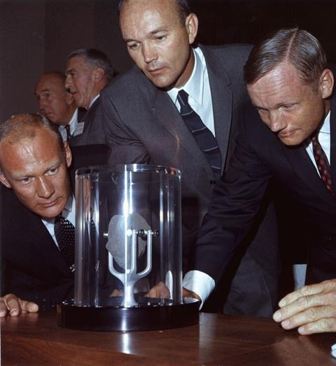 An image showing the Apollo 11 crew looking at a lunar sample