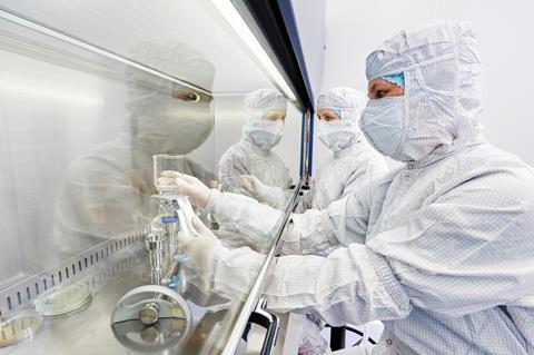 A photograph of laboratory researchers in protective uniform