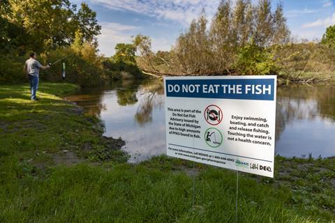 An image showing a sign that warns against eating the fish inside a river, as it is contaminated with PFAS