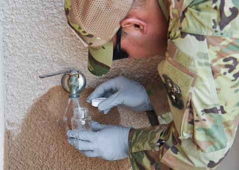 An image showing a member of the military taking a water sample