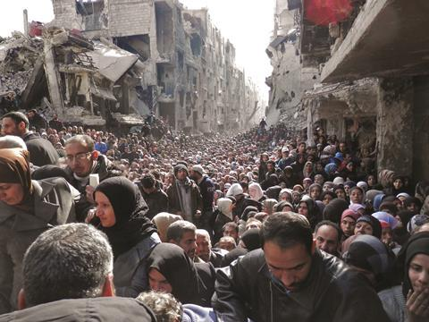Residents wait in line to receive food aid distributed in the Yarmouk refugee camp in Damascus, Syria
