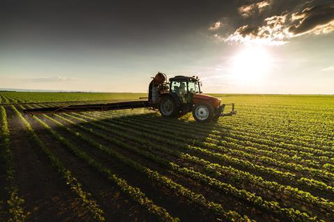 An image showing a tractor spraying crops