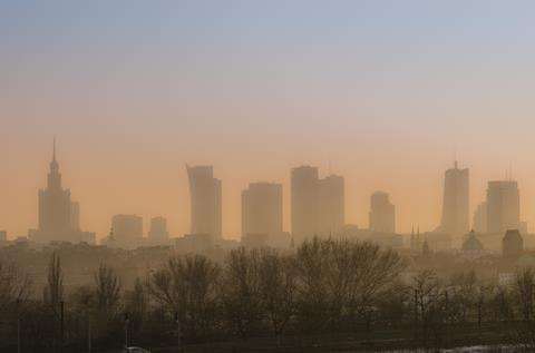 View across Warsaw skyline showing in sunset with smog and dust in the air